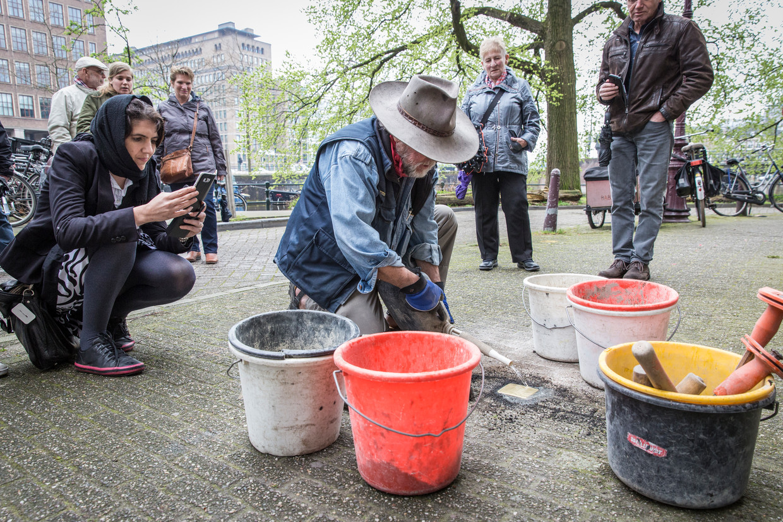 Gunther Demnig plaatst een Stolpersteine in de stoep bij Spinozastraat in 2017. Beeld Dingena Mol