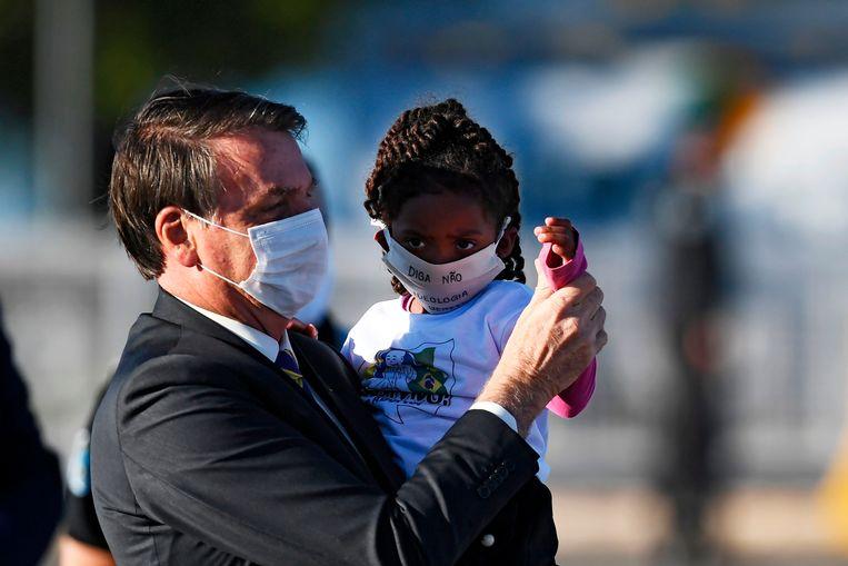 De Braziliaanse president Jair Bolsonaro tilt een meisje op. Beide dragen een mondkapje.