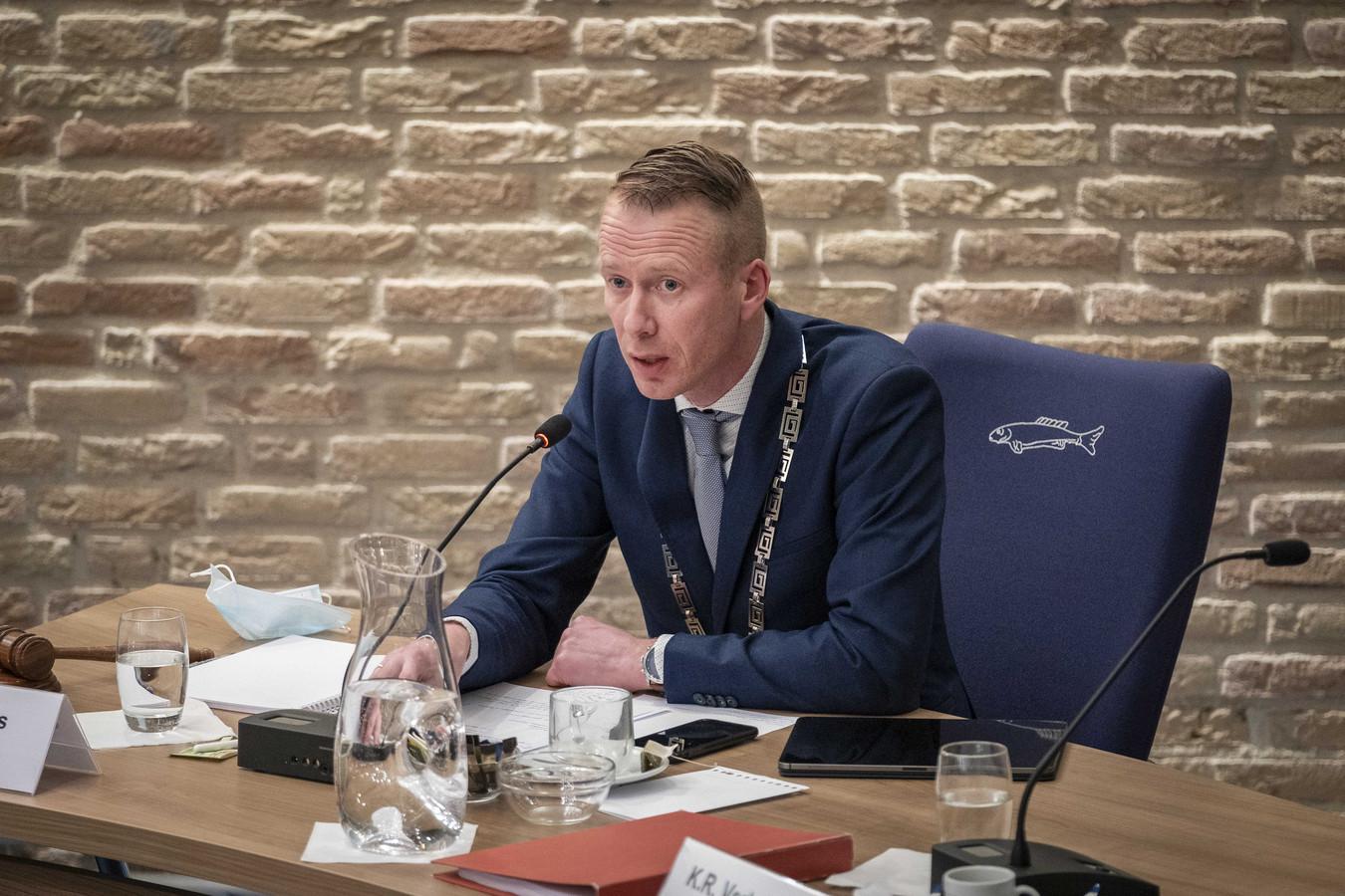 Burgemeester Cees van den Bos tijdens een spoeddebat over de rellen tegen de avondklok. Bij de rellen vernielden relschoppers politieauto's, belaagden zij een cameraploeg van de NOS en werd een testlocatie van de GGD in brand gestoken.