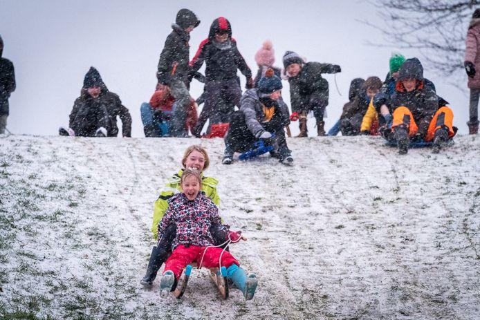 Kinderen genieten met hun sleeën  van het beetje sneeuw dat zaterdagmiddag valt op de speelplaats aan de Plantagepolder.