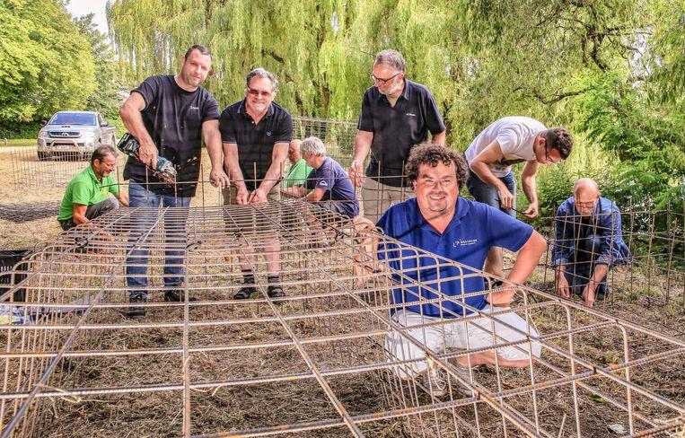Vrijwilligers helpen kooien maken die de vissen tegen aalscholvers moeten beschermen.