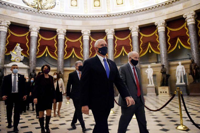 Vicepresident Mike Pence (met blauwe das) loopt woensdag door het Capitool met een stoet ambtenaren die de stemmen bij zich hebben van het College van Kiesmannen, ter bekrachtiging van de verkiezing van Joe Biden tot president. Beeld AFP