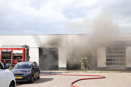 De bramdweer bestrijdt de brand bij de Citroen-garage in Tiel door de roldeuren.