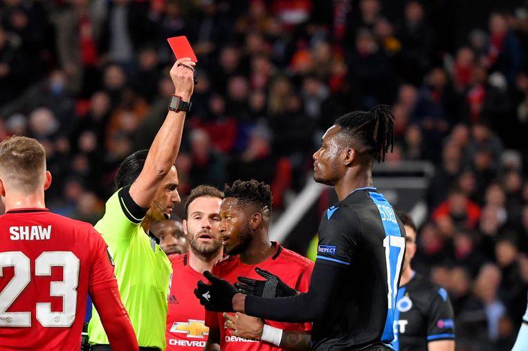 De ref deelt een rode kaart uit aan Simon Deli. Beeld Photo News
