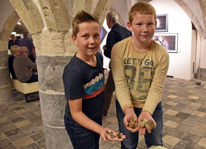 Tijdens de eerste Archeologiemiddag in het belfort namen Loep (l) en Tibo (r) hun vondsten mee, om te laten zien aan archeologen.