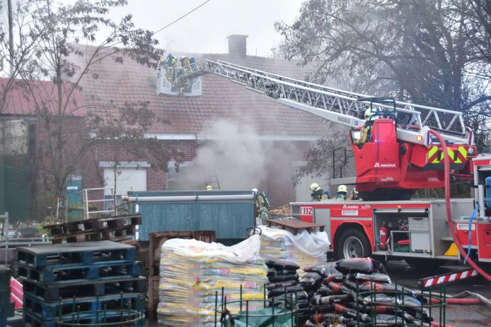 De brandweer bij het bijna honderd jaar oude huis waaruit veel rook ontsnapt.