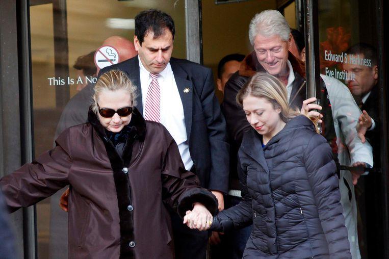 Hillary Clinton verlaat met haar man Bill en dochter Chelsea het ziekenhuis in New York. Beeld REUTERS