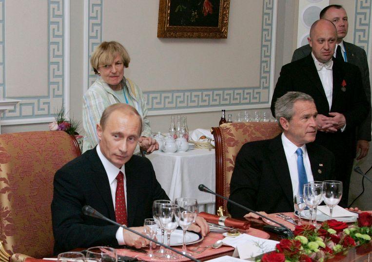 Poetin ontvangt George W. Bush, met op de achtergrond Prigozjin. Beeld AP