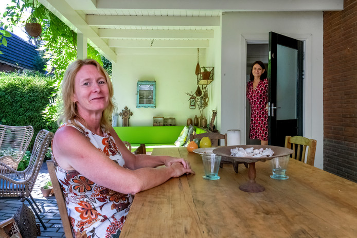 Marieke Kleiboer doet de deur open van haar aan Aisha verhuurde tuinhuis. Links projectleider Bianca van der Neut.