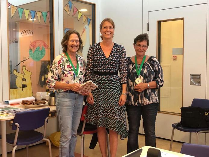 Joke Verkuijlen (links) en Laura Kool Hoogerheide (rechts) werden donderdagmiddag verrast door wethouder Anita Sørensen van de gemeente Maasdriel.