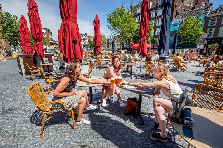 De eerste klanten op het terras van Café de Beurs genieten van het eerste biertje. Beeld Raymond Rutting / de Volkskrant