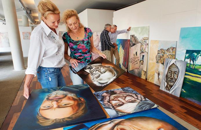 Henriëtte Dobbelsteen uit Veghel (links) bekijkt werk van Hannie Roefs uit Loosbroek. Zijn zijn twee van de twaalf kunstenaars