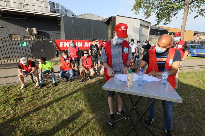 Productiemedewerkers van tabaksverwerker HTL & DHT (Deli HTL) in Eindhoven staken de hele week voor een betere cao. Op de voorgrond staat links Frank van Dijk, rechts Edgar Blanquicet-Acosta.