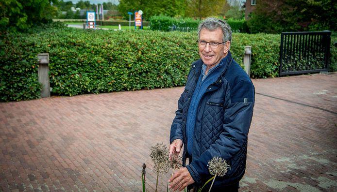 Ben van Ooijen voor zijn huis en op de achtergrond de entree van de Tuinen Appeltern.