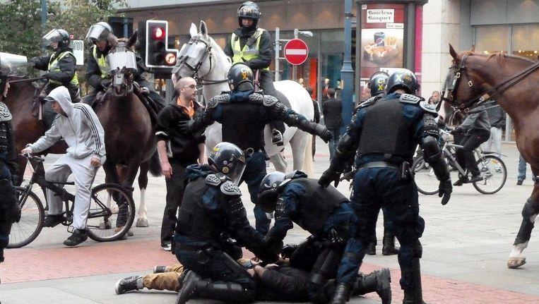 Politieagenten proberen een man in Manchester in bedwang te houden. Beeld EPA