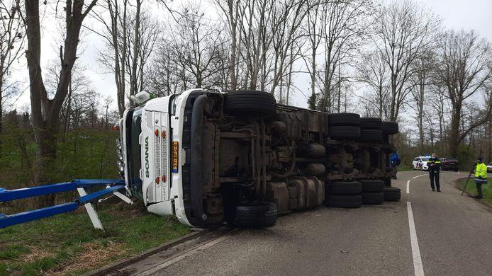 Door nog onbekende oorzaak kwam de vrachtwagen op z'n kant terecht.