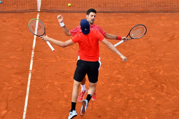 Djokovic en Krajinovic innig met de borst tegen elkaar na een gewonnen punt tijdens de Adria Tour in Belgrado. Beeld AFP