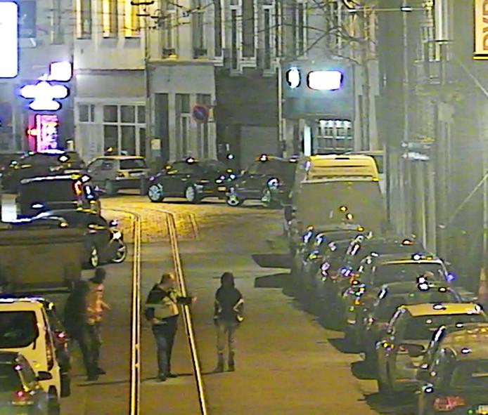De politie is op zoek naar de man die in het midden loopt.