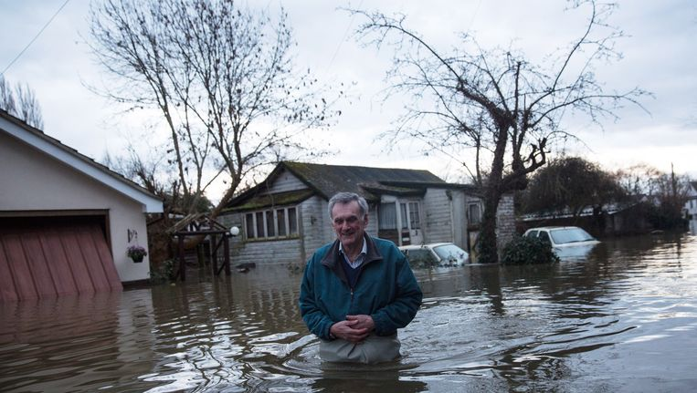 Een inwoner van Shepperton waadt maandag door het nog steeds stijgende water. Beeld Getty Images