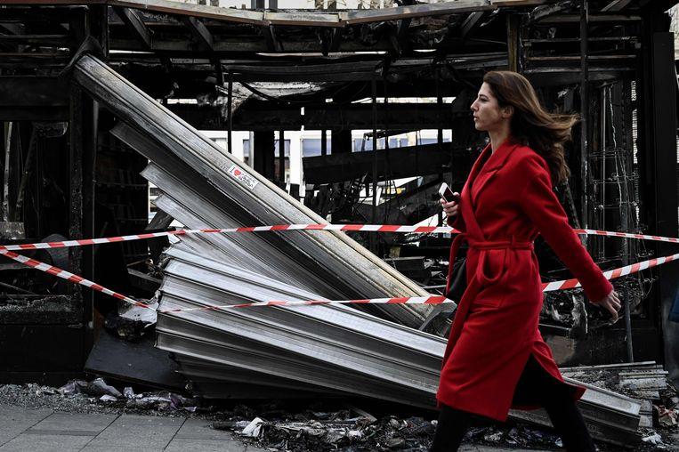 Een uitgebrande kiosk maandag op de Champs Elysées in Parijs. Beeld AFP