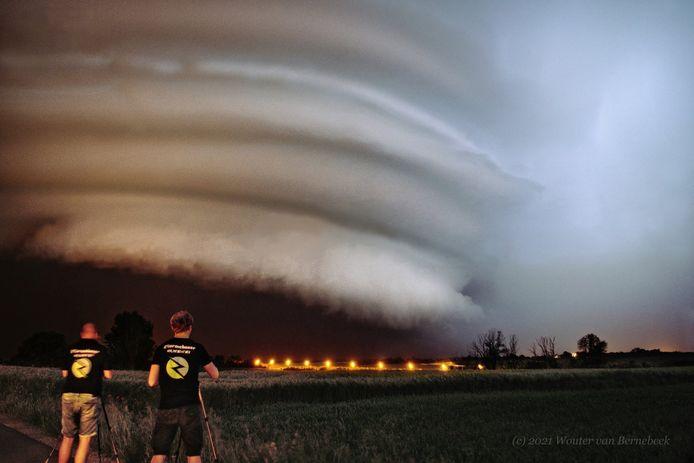 Stormchaser Brian Verhoeven (rechts) met op de achtergrond een supercell in België.