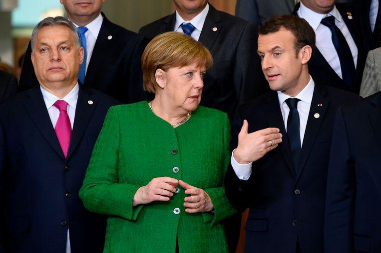 De Hongaarse premier Viktor Orbán, de Duitse Bondskanselier Angela Merkel en de Franse President Emmanuel Macron bij de Europese Commissie in Brussel in februari. Hongarije dreigt nu gestraft te worden voor het beleid van Orbán. Beeld AFP