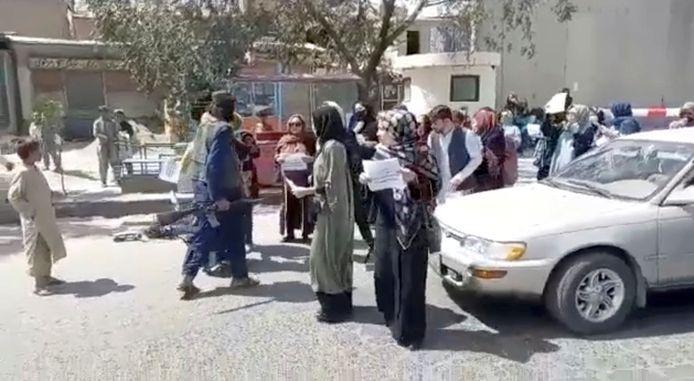 Op een still uit een video is te zien hoe een gewapende talibanstrijder richting een groep protesterende vrouwen stapt.