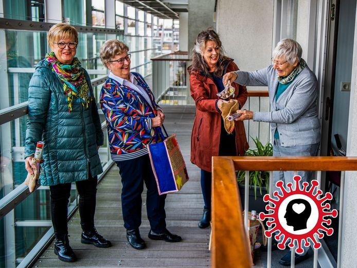 Betsy Ruijgt (72, met tas) bezorgt met de feestcommissie een aardigheidje bij buren.