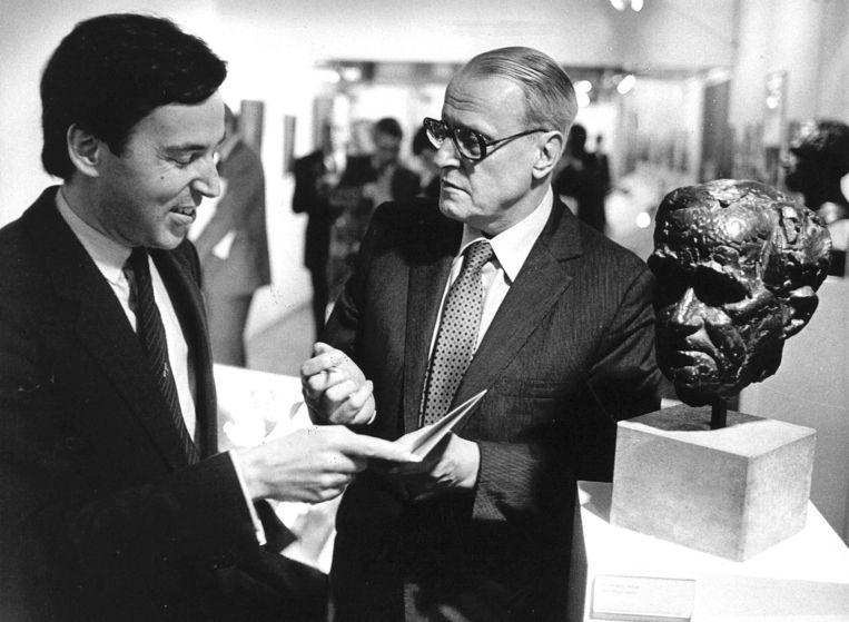 W.F. Hermans geeft toenmalig minister van cultuur Elco Brinkman een gesigneerd exemplaar van 'Relikwieen en Documenten'. Rechts een bronzen kop  van dichter A. Roland Holst. Beeld anp