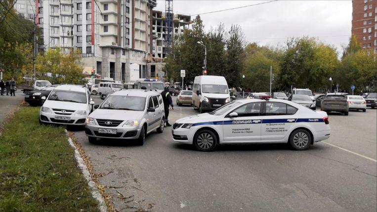 Politieauto's blokkeren de weg bij de universiteit van Perm, waar een schutter maandagochtend het vuur opende. Beeld REUTERS