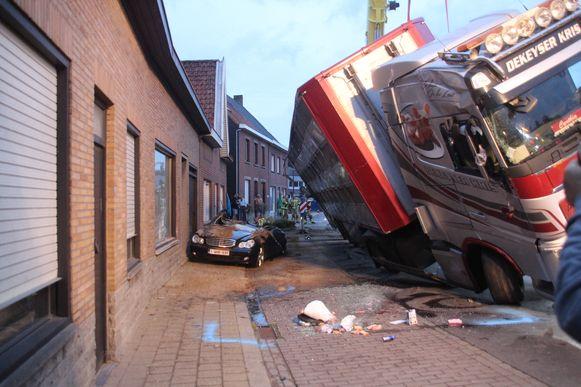 Vrachtwagen met 210 varkens kantelt tegen woning en op auto.