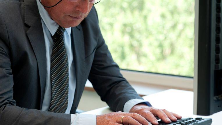 Een oudere man aan een computer.