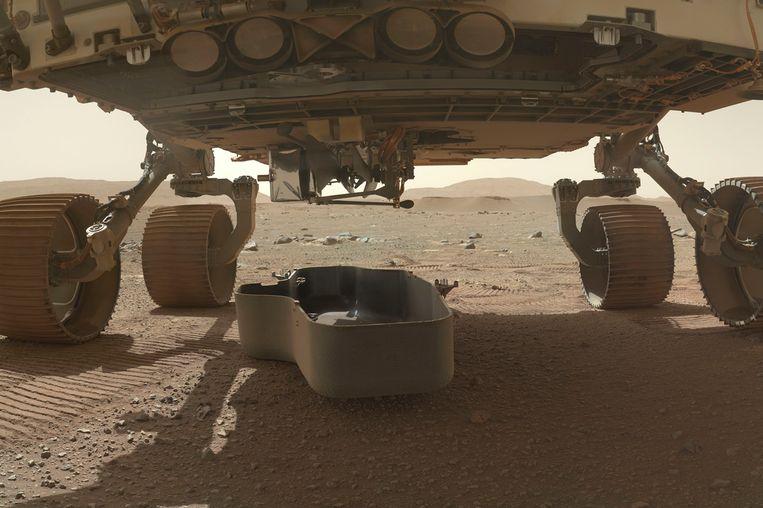 Een beschermingsschild is dit weekend vrijgekomen, waardoor de kleine helikopter onderaan de Marsrover nu zichtbaar is.  Beeld AP