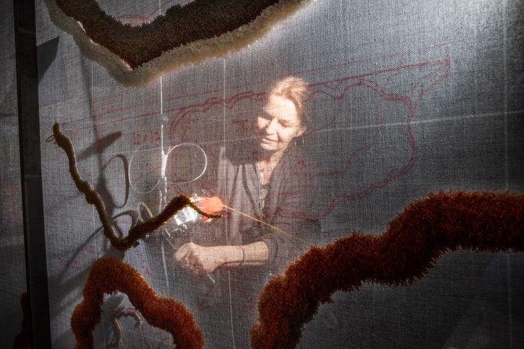 Lizan Freijsen staat aan de achterkant van het tapijt, nu nog opgespannen op een raster. Beeld Pauline Niks