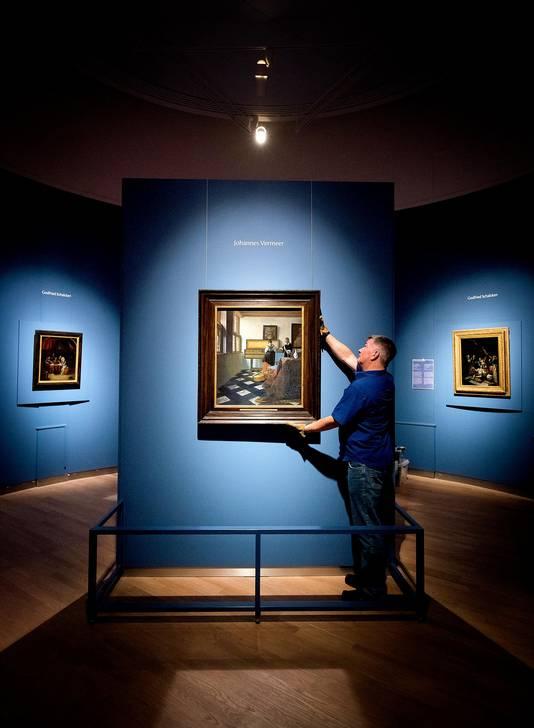 De Muziekles van Johannes Vermeer wordt recht gehangen tijdens de opbouw van de tentoonstelling Hollanders in huis: Vermeer en tijdgenoten uit de Britse Royal Collection in het Mauritshuis.