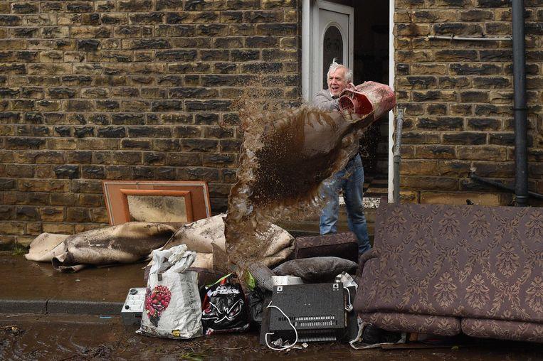 Een bewoner van het Engelse Mytholmroyd giet een emmer water uit over het puin dat de storm veroorzaakte. Beeld AFP