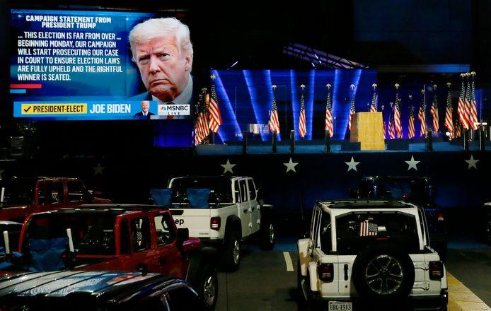 Auto's in de rij voor het podium waar Biden spreekt. Op schermen de tv-registraties van 'Election Night'.