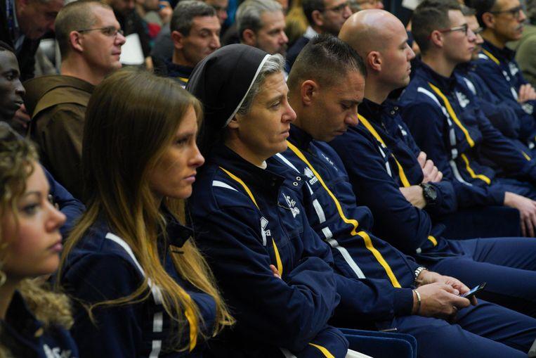 Leden van de atletiekploeg 'Athletica Vaticana' wonen de persconferentie bij. Beeld AP