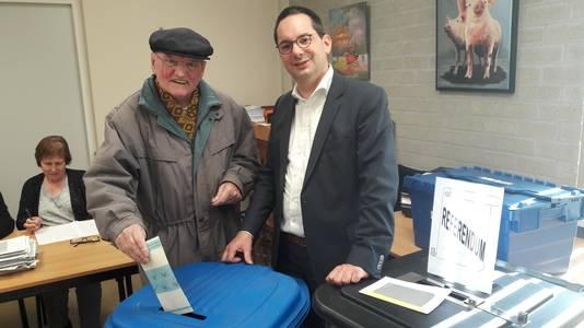 """Bij De Kloek in Huijbergen komt Cees Uijtdewilligen - ,,80 jaar en al 64 jaar broeder hier"""" - zijn stem uitbrengen in het bijzijn van burgemeester Steven Adriaansen."""