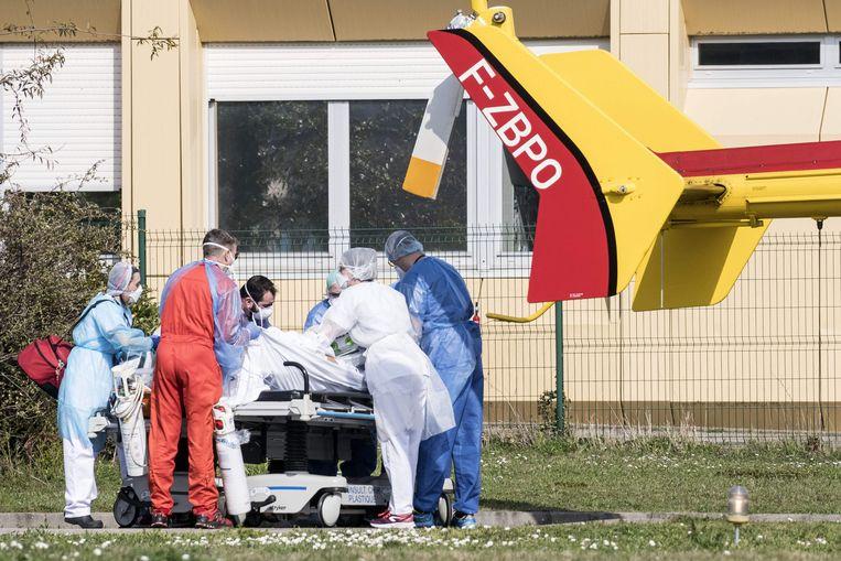 Een coronapatiënt wordt vanuit het ziekenhuis in Mulhouse een brancard naar een medische helikopter gebracht. Beeld AFP
