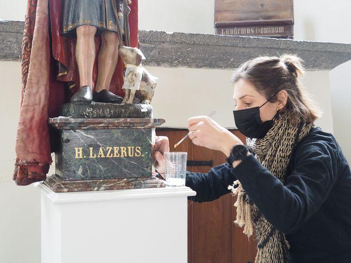 Katrien Van Den Bosch van Artecura bereidt het beeld van H. Lazarus voor voor transport.