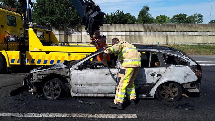 De uitgebrande auto bij Staphorst wordt weggehaald.