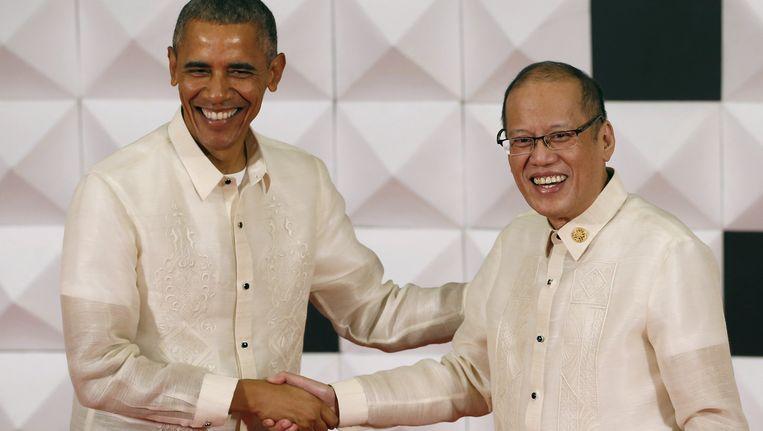 Obama, in een traditioneel Filipijns baronghemd, schudt de hand van de Filipijnse president Benigno Aquino op het galadiner van de Asia-Pacific Economic Cooperation. Beeld REUTERS