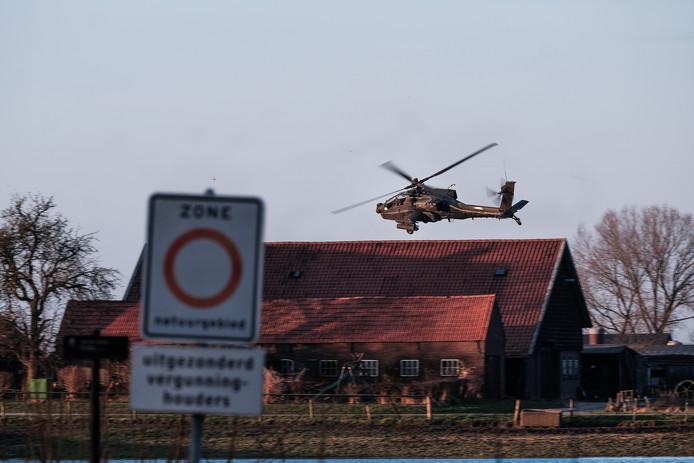 Een Apache van defensie boven een boerderij in de Fraterwaard in Doesburg.