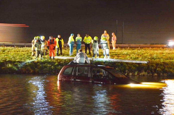 In afwachting van hulp zat de man op het dak van zijn auto.