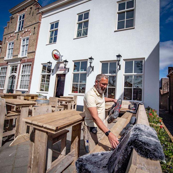Niek Bruijs, eigenaar van Café De Kaai , maakt z'n terras in orde.