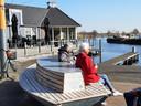 Janny Groen en Joke Blom op een bankje in Nieuwkoop, naast het lege terras van restaurant LKKR.