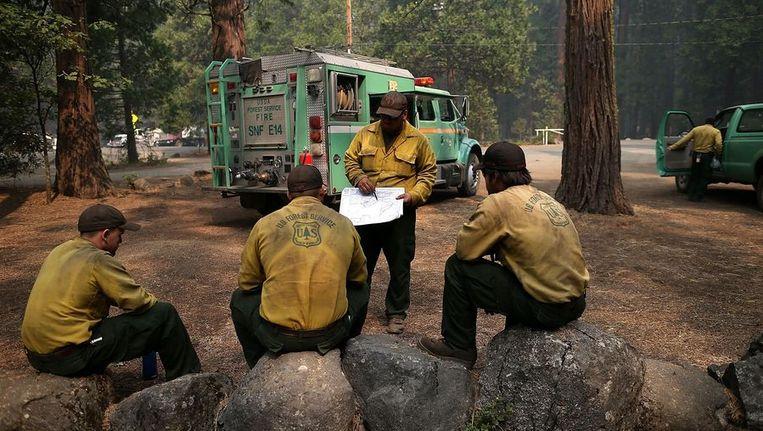 Brandbestrijders van de US Forest Service pauzeren even in Camp Mather bij Groveland, Californië. Beeld afp