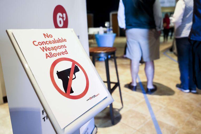 Een bordje aan het stembureau in Charleston duidt op een verbod op verhulde wapens.   Beeld AFP