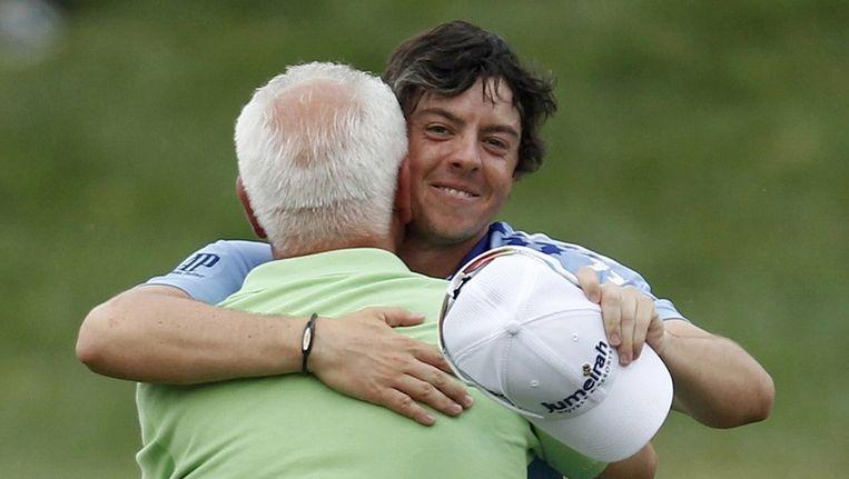 Rory McIlroy omhelst, na zijn overwinning in de US Open, zijn vader Gerry. Beeld reuters